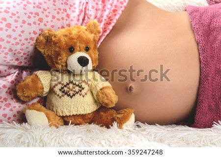 Close-up of a pregnant woman in pink pajamas and toy bear - stock photo