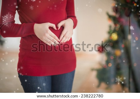 Close up of a pregnant woman making a heart on her belly against snow falling - stock photo