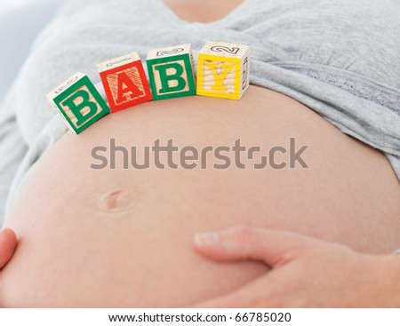 Close up of a pregnant woman with baby letters on her belly on the bed - stock photo