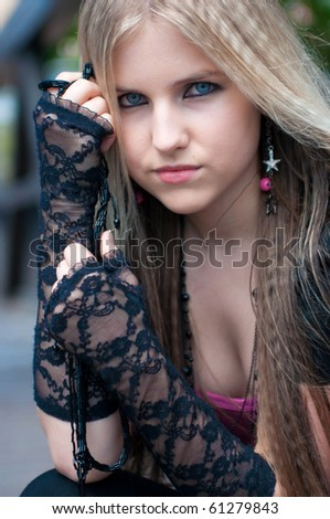 Close-up of a pretty blond girl with long black gloves - stock photo