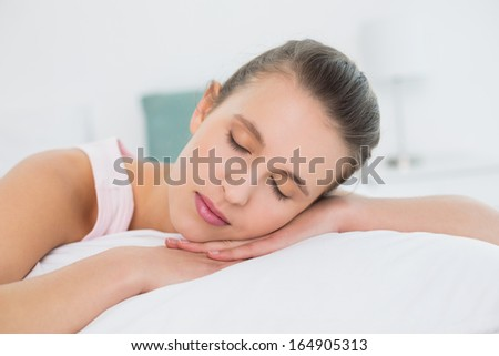 Close-up of a pretty young woman sleeping with eyes closed in bed