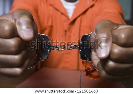 Close up of a prisoner hand's fettered with handcuffs - stock photo