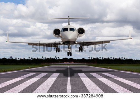 Close up of a private jet landing - stock photo