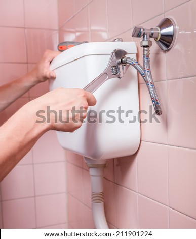 Close-up of a professional toilet reparation, vertical - stock photo