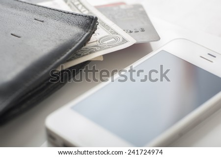 Close up of a purse, dollar, credit cards and a smart phone with shallow depth of field, can be used to stress mobile payment - stock photo
