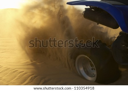 Close-up of a quad bike spraying up sand in desert