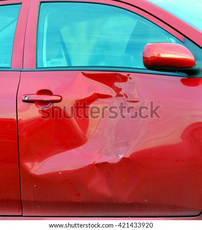 Close up of a red automobile door with large dent damage from a collision.