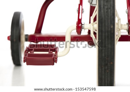 Close up of a red child's tricycle on a white background, with the focus on the pedal - stock photo