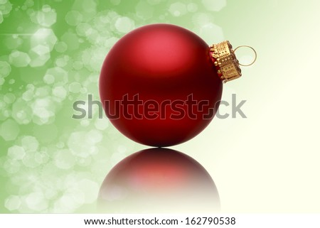 close up of a red christmas ball with blurred green background.