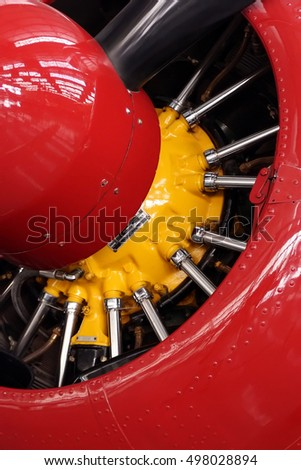 Close-up of a red propeller nose with a yellow engine and metal bars