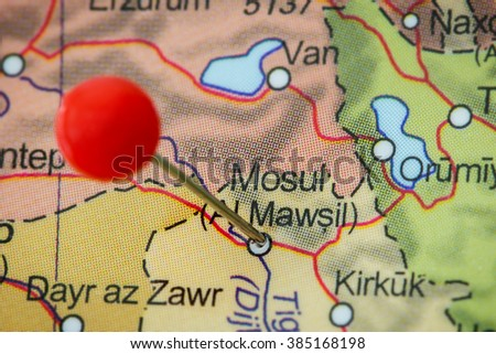 Close-up of a red pushpin in a map of Mosul, Iraq.