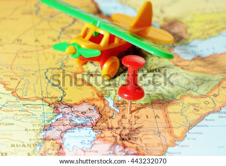 Close-up of a red pushpin on a map of Kenia  Africa and airplane toy- travel concept - stock photo