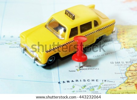 Close-up of a red pushpin on a map of Madeira island and taxi car - travel concept - stock photo