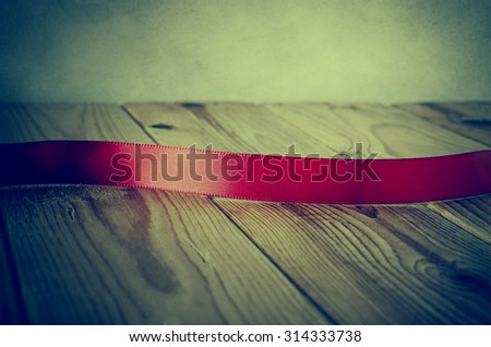 Close up of a red satin ribbon on an old wood plank table. Facing front to provide copy space for a message.  Parchment background. Cross processed with vignette for retro or vintage style. - stock photo