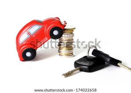 close-up of a red toy car on a pile of euro coins with car keys in the foreground on a white background.  - stock photo