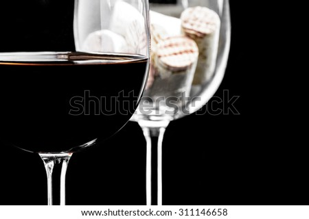 Close-up of a red wine glass and corks on a black background