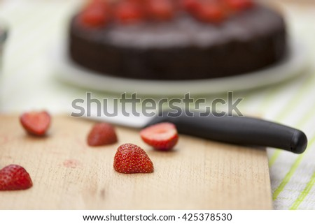 Close up of a ripe halved topped strawberry on a chopping board with a knife and a chocolate cake in the background - stock photo