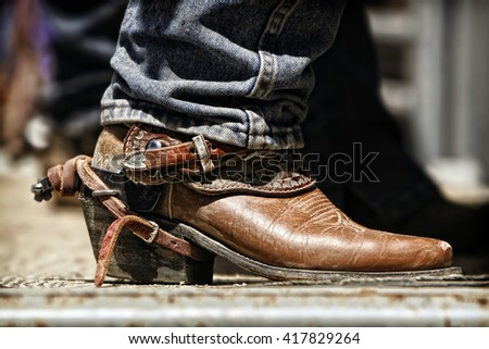 Close up of a rodeo cowboy's boot and spur as he prepares behind the chutes for an upcoming ride. - stock photo