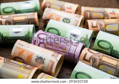 Close-up Of A Rolled Euro Banknotes On Wooden Desk - stock photo