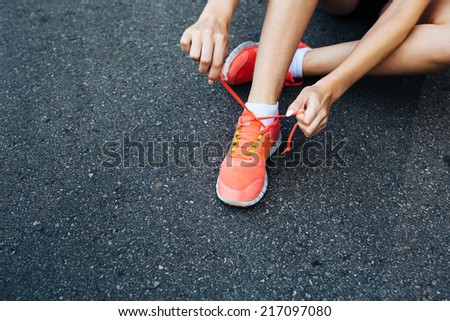 Close-up of a runner lacing her shoes - stock photo