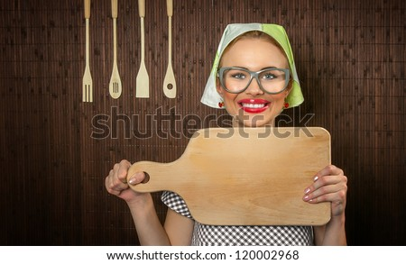 Close-up of a rural funny woman cook with kitchen cutting board - stock photo