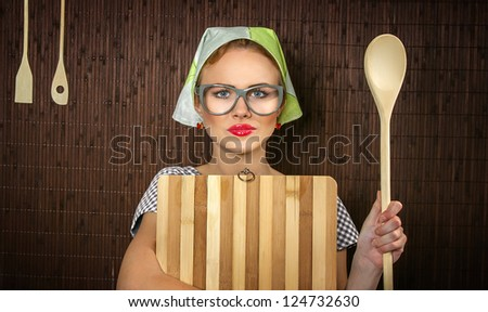 Close-up of a rural funny woman cook with kitchen cutting board and ladle - stock photo