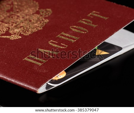 Close-up of a Russian passport cover with a plastic card embedded in it . Text on Russian: PASSPORT.
