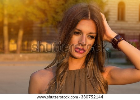 Close-up of a sad and depressed woman deep in thought outdoors. - stock photo