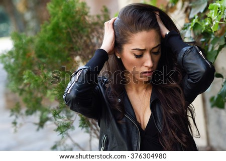 Close-up of a sad and depressed woman deep in thought outdoors. Girl with her hands on head - stock photo