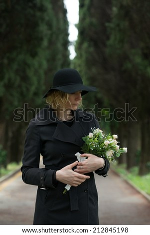 Close-up of a sad woman at cemetery holding flowers - stock photo