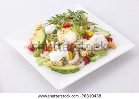 Close-up of a salad with egg and shrimps, pea, avocado, pasta - stock photo