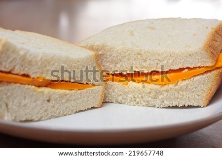 Close-up of a sandwich made with red leicester cheese and thick white bread - stock photo