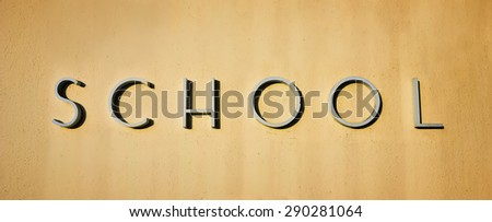 Close up of a school sign on a wall.  - stock photo