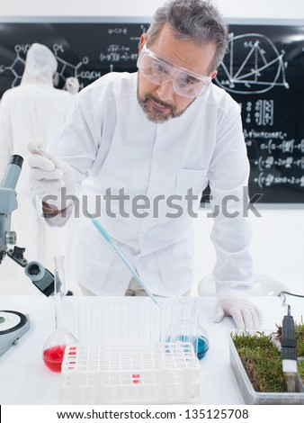 close-up of a scientist in a chemistry lab analyzing colorful liquids on a lab table with another one on the background  writing formulas on a blackboard - stock photo