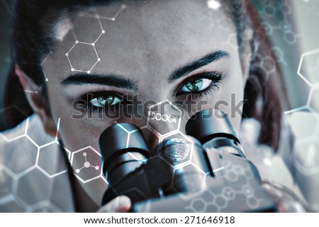 Close up of a scientist posing with a microscope against science and medical graphic - stock photo