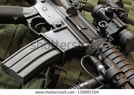 Close-up of a scratched M4A1 (AR-15) carbine and green military tactical vest - stock photo