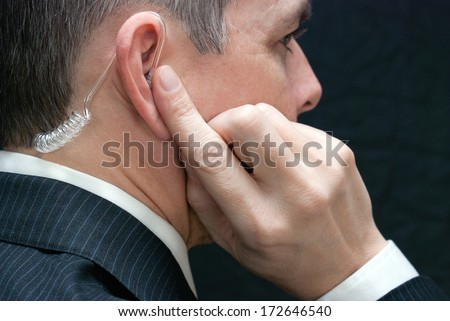 Close-up of a secret service agent listening to his earpiece, close side.