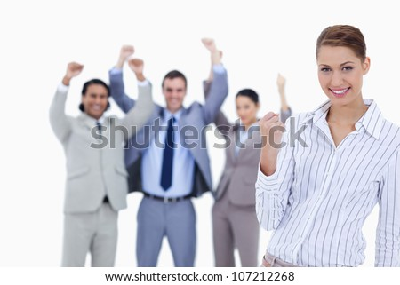 Close-up of a secretary smiling and clenching her fist with enthusiastic business people with their arms raised against white background - stock photo