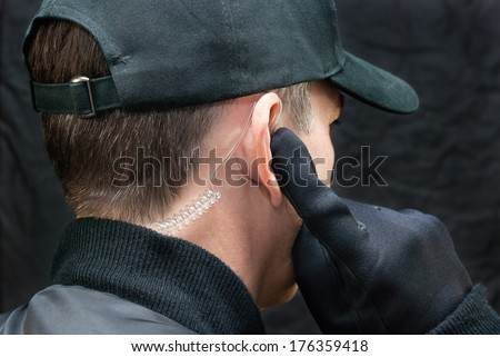 Close-up of a security guard listening to his earpiece. Shot from, over the shoulder. - stock photo