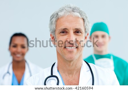 Close up of a senior Doctor standing in front of his team - stock photo