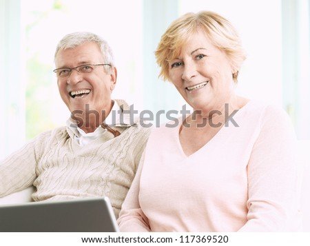Close up of a senior happy couple in front of a laptop - stock photo