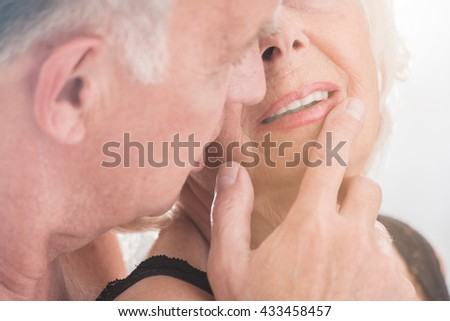 Close up of a senior man touching gently woman's lips