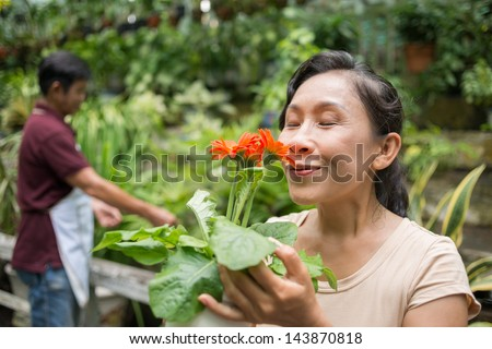 Close-up of a senior woman enjoying the flower's fragrance on the foreground - stock photo