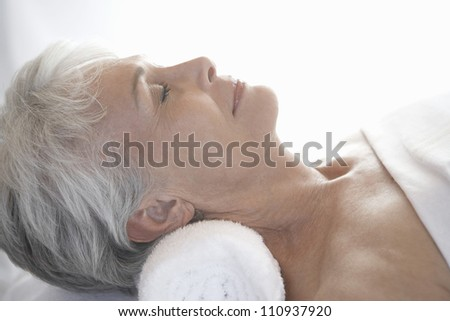 Close-up of a senior woman relaxing on message table - stock photo