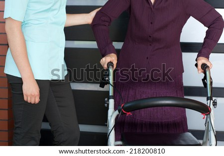 Close-up of a senior woman with orthopedic walker and nurse - stock photo