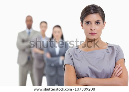 Close-up of a serious business team crossing their arms and standing behind each other with focus on the foreground woman - stock photo