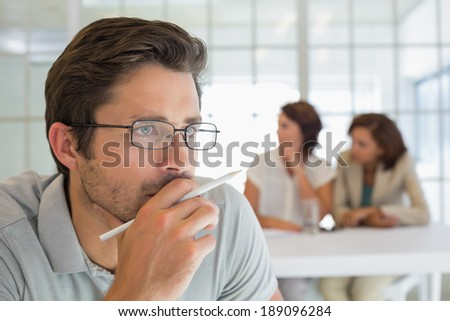 Close-up of a serious businessman with colleagues in meeting in background at the office - stock photo