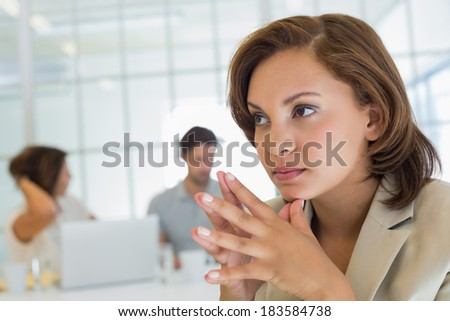 Close-up of a serious businesswoman with colleagues in meeting in background at the office - stock photo