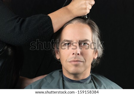 Close-up of a serious man looking to camera while his long hair is shaved off for a cancer fundraiser. - stock photo