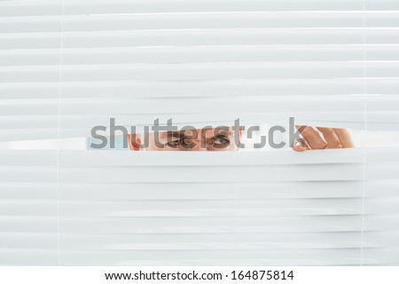 Close-up of a serious mature businessman peeking through blinds in the office - stock photo